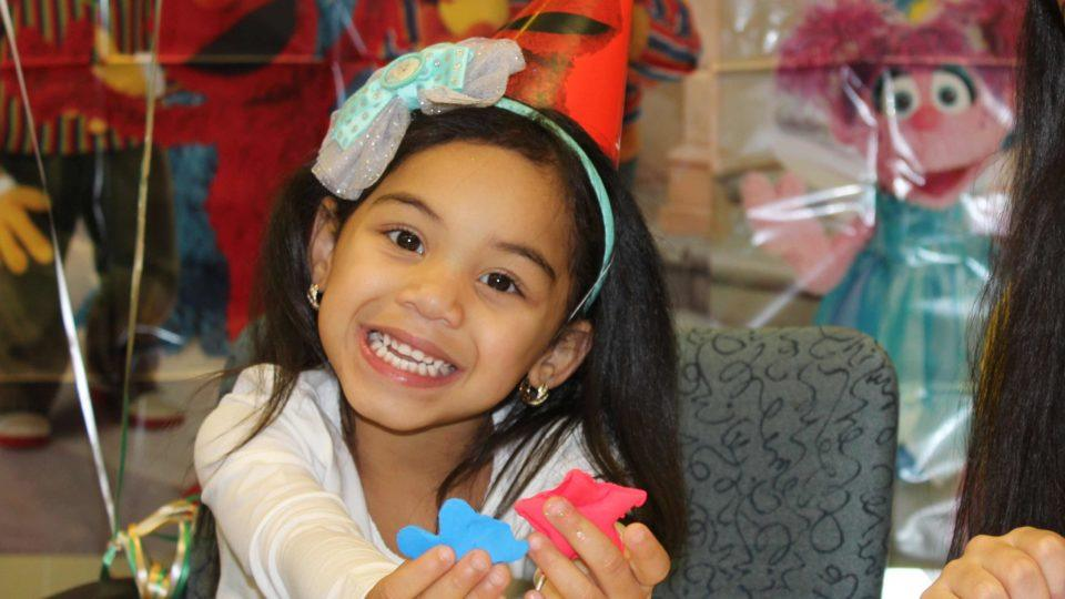 Pediatric patient smiles while wearing Elmo birthday hat holds up shapes made from play dough